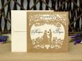 Лазерно изрязана сватбена покана в перлено злато с декорация от флорални елементи, сърчица и младоженци